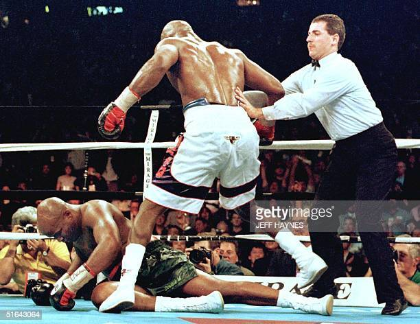 Evander Holyfield is pushed away by referee Mitch Halpern after Holyfield knocked down Michael Moorer for the second time in the eighth round of...