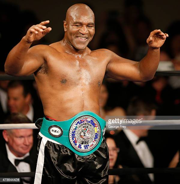 Evander Holyfield shows off his boxing belt after a fight with Mitt Romney during a charity boxing event on May 15 2015 in Salt Lake City Utah The...