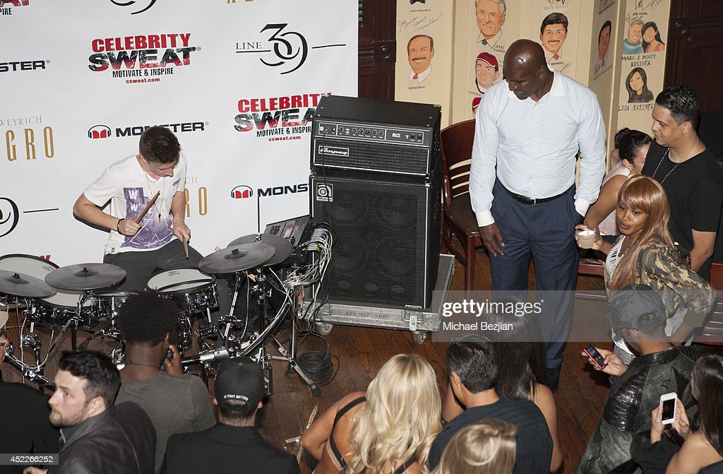 Evander Holyfield watches drummer Justin Charney perform at PREFUNC At The Celebrity Sweat VIP Party at The Palm on July 16, 2014 in Los Angeles, California.