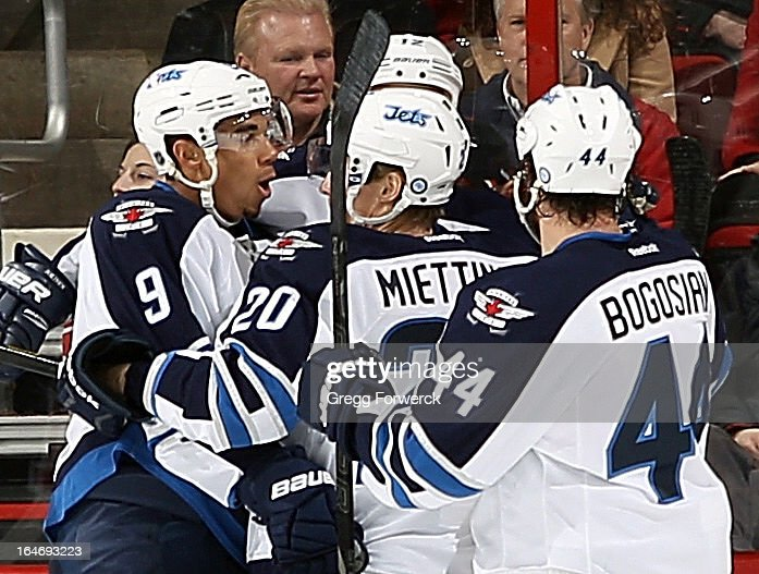 Evander Kane #9, Antti Miettinen #20 and Zach Bogosian #44 of the Winnipeg Jets surround Olli Jokinen #12 following his first-period goal against the Carolina Hurricanes during their NHL game at PNC Arena on March 26, 2013 in Raleigh, North Carolina.
