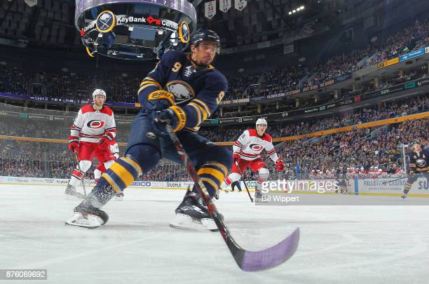 Evander Kane of the Buffalo Sabres chases the puck using lavender tape on his hockey stick on Hockey Fights Cancer Night during an NHL game against...