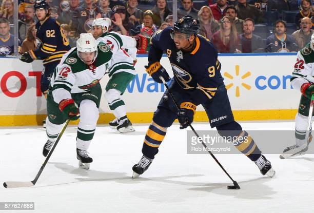 Evander Kane of the Buffalo Sabres fires a shot while defended by Eric Staal of the Minnesota Wild during an NHL game on November 22 2017 at KeyBank...