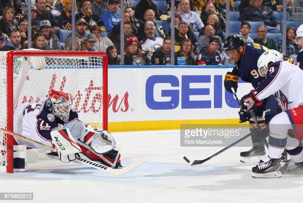 Evander Kane of the Buffalo Sabres is defended by Artemi Panarin and Sergei Bobrovsky of the Columbus Blue Jackets during an NHL game on November 20...