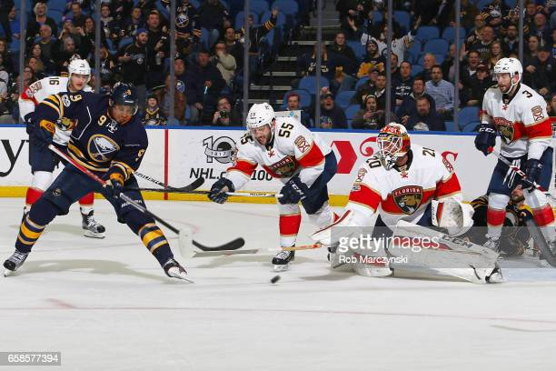 Evander Kane of the Buffalo Sabres is stopped by Jason Demers and Reto Berra of the Florida Panthers during an NHL game at the KeyBank Center on...