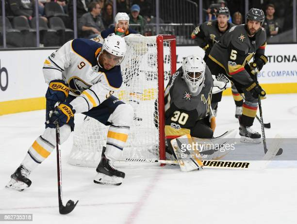 Evander Kane of the Buffalo Sabres prepares to take a shot against Malcolm Subban of the Vegas Golden Knights as Deryk Engelland of the Golden...