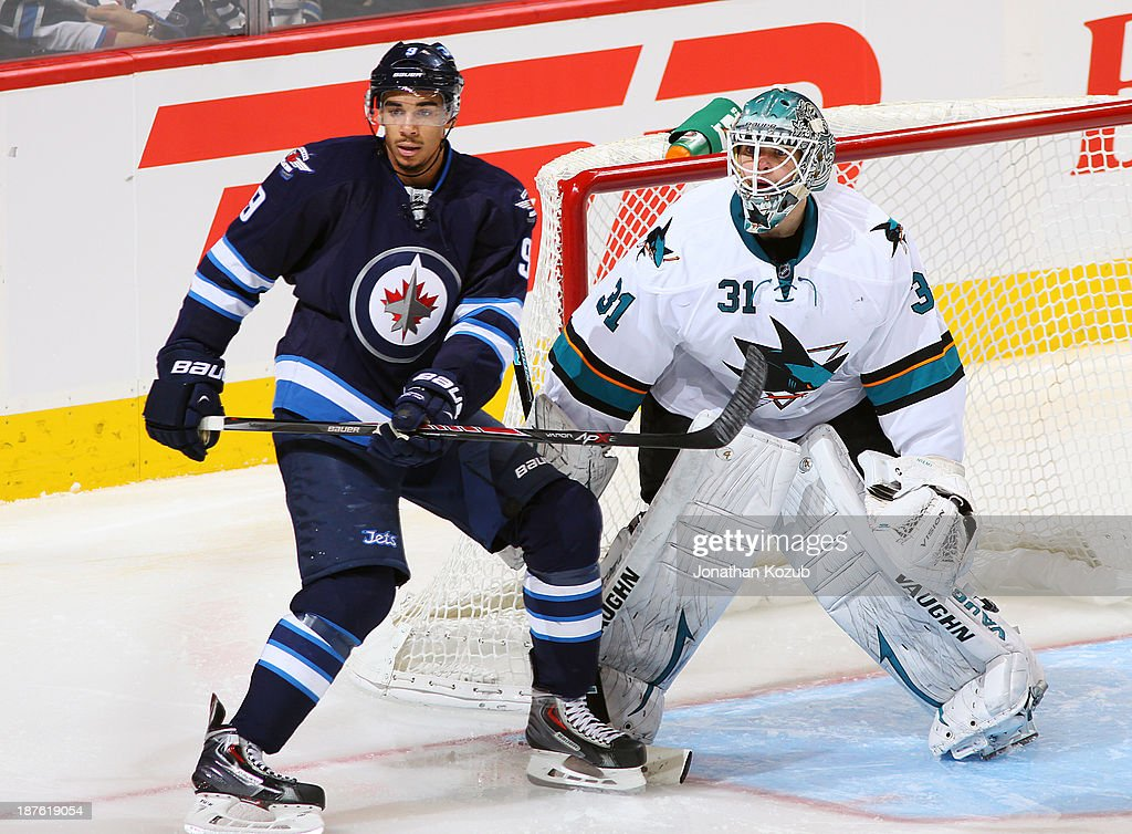 <a gi-track='captionPersonalityLinkClicked' href=/galleries/search?phrase=Evander+Kane&family=editorial&specificpeople=4303789 ng-click='$event.stopPropagation()'>Evander Kane</a> #9 of the Winnipeg Jets and goaltender <a gi-track='captionPersonalityLinkClicked' href=/galleries/search?phrase=Antti+Niemi&family=editorial&specificpeople=213913 ng-click='$event.stopPropagation()'>Antti Niemi</a> #31 of the San Jose Sharks keep an eye on the play during second period action at the MTS Centre on November 10, 2013 in Winnipeg, Manitoba, Canada.