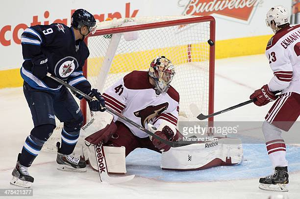 Evander Kane of the Winnipeg Jets and Mike Smith of the Phoenix Coyotes watch the puck hit the post in thirdperiod action in an NHL game at the MTS...