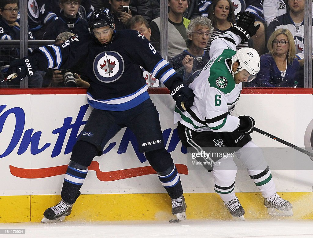 Evander Kane #9 of the Winnipeg Jets and Trevor Daley #6 of the Dallas Stars collide against the boards in second-period action of an NHL game at the MTS Centre on October 11, 2013 in Winnipeg, Manitoba, Canada.