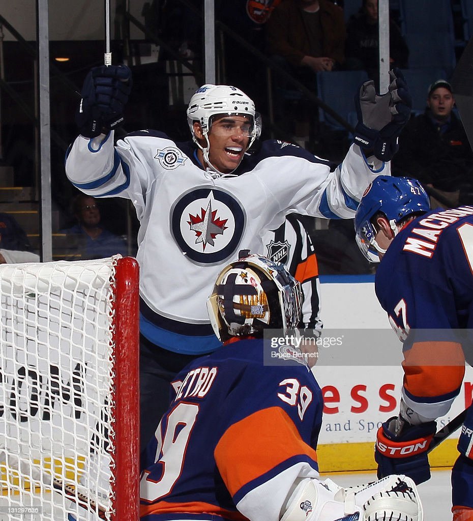 Evander Kane #9 of the Winnipeg Jets celebrates a goal by Johnny Oduya #29 (not shown) at 16:04 of the third period against Rick DiPietro #39 of the New York Islanders at the Nassau Veterans Memorial Coliseum on November 3, 2011 in Uniondale, New York. The Jets defeated the Islanders 3-0.