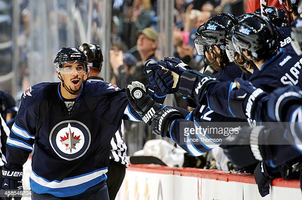 Evander Kane of the Winnipeg Jets celebrates his third period goal against the Pittsburgh Penguins with teammates at the bench on November 6 2014 at...