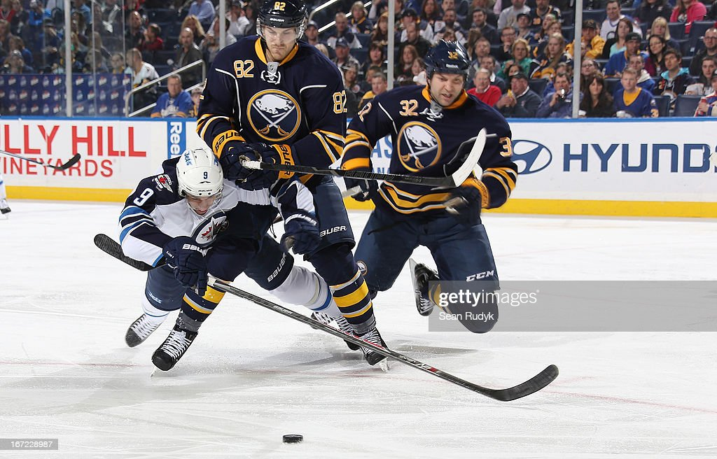 <a gi-track='captionPersonalityLinkClicked' href=/galleries/search?phrase=Evander+Kane&family=editorial&specificpeople=4303789 ng-click='$event.stopPropagation()'>Evander Kane</a> #9 of the Winnipeg Jets dives to reach for the puck against <a gi-track='captionPersonalityLinkClicked' href=/galleries/search?phrase=Marcus+Foligno&family=editorial&specificpeople=5662790 ng-click='$event.stopPropagation()'>Marcus Foligno</a> #82 of the Buffalo Sabres as teammate John Scott #32 watches on at First Niagara Center on April 22, 2013 in Buffalo, New York. Winnipeg defeated Buffalo, 2-1.