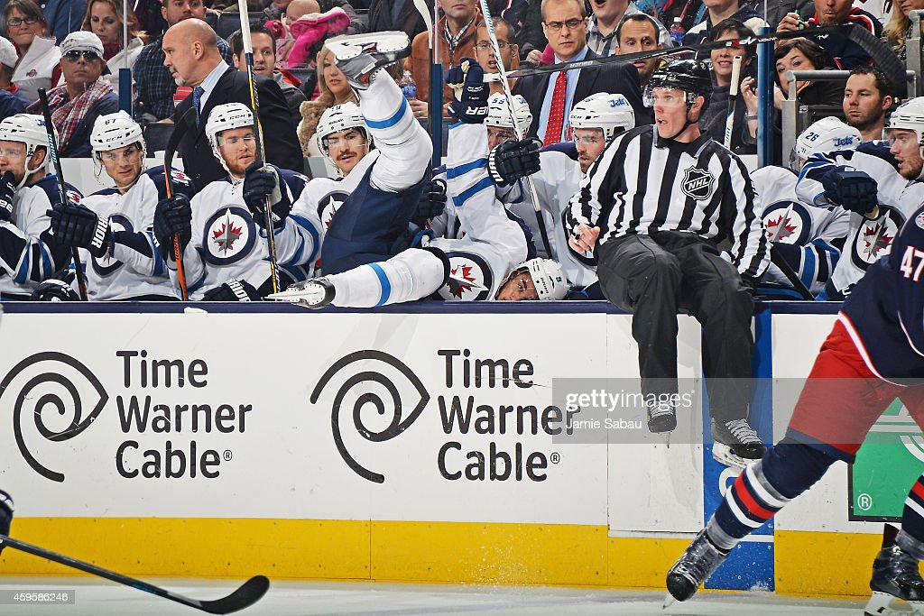Evander Kane #9 of the Winnipeg Jets falls into his bench after being checked during the second period of a game against the Columbus Blue Jackets on November 25, 2014 at Nationwide Arena in Columbus, Ohio.