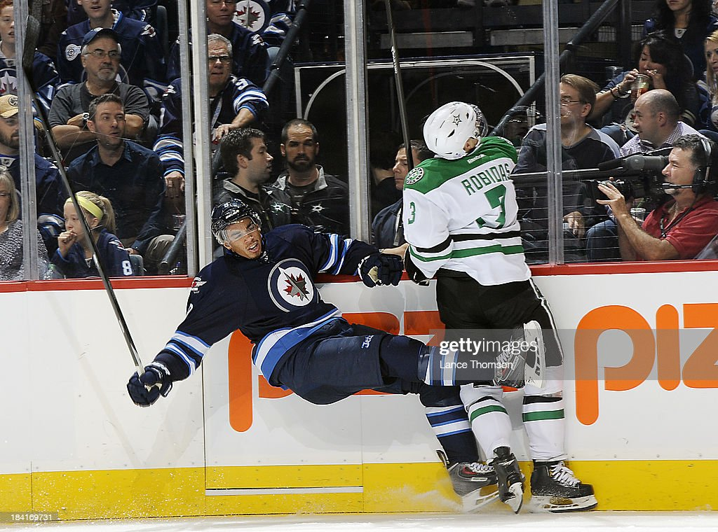 Evander Kane #9 of the Winnipeg Jets falls to the ice after colliding along the boards with Stephane Robidas #3 of the Dallas Stars during first period action at the MTS Centre on October 11, 2013 in Winnipeg, Manitoba, Canada.