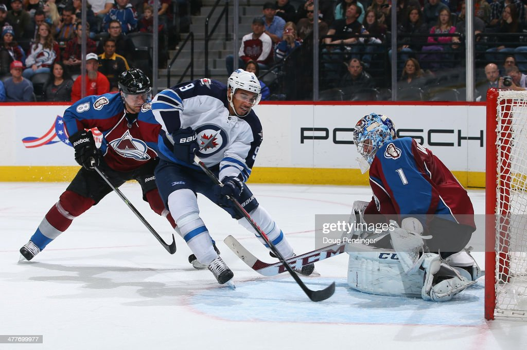 Evander Kane #9 of the Winnipeg Jets gets off a shot and goalie Semyon Varlamov #1 of the Colorado Avalanche makes the save as Jan Hejda #8 of the Colorado Avalanche follows the play at Pepsi Center on March 10, 2014 in Denver, Colorado.