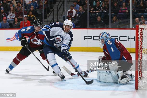 Evander Kane of the Winnipeg Jets gets off a shot and goalie Semyon Varlamov of the Colorado Avalanche makes the save as Jan Hejda of the Colorado...