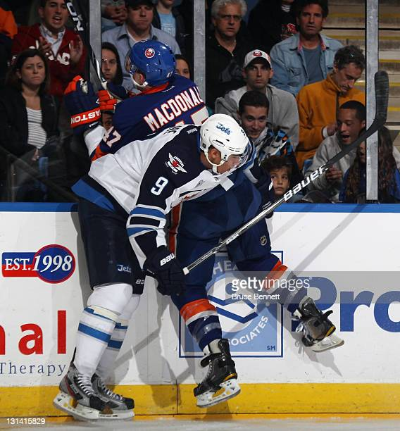 Evander Kane of the Winnipeg Jets hits Andrew MacDonald of the New York Islanders at the Nassau Veterans Memorial Coliseum on November 3 2011 in...
