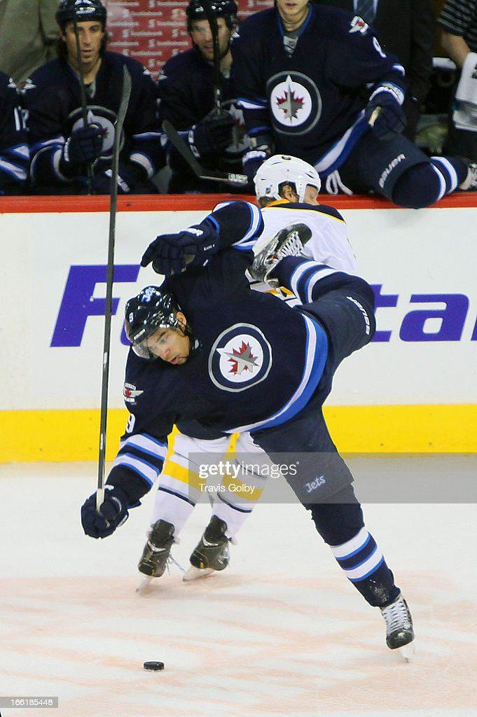 Evander Kane #9 of the Winnipeg Jets is upended by Steve Ott #9 of the Buffalo Sabres in front of the bench during third-period action at the MTS Centre on April 9, 2013 in Winnipeg, Manitoba, Canada.