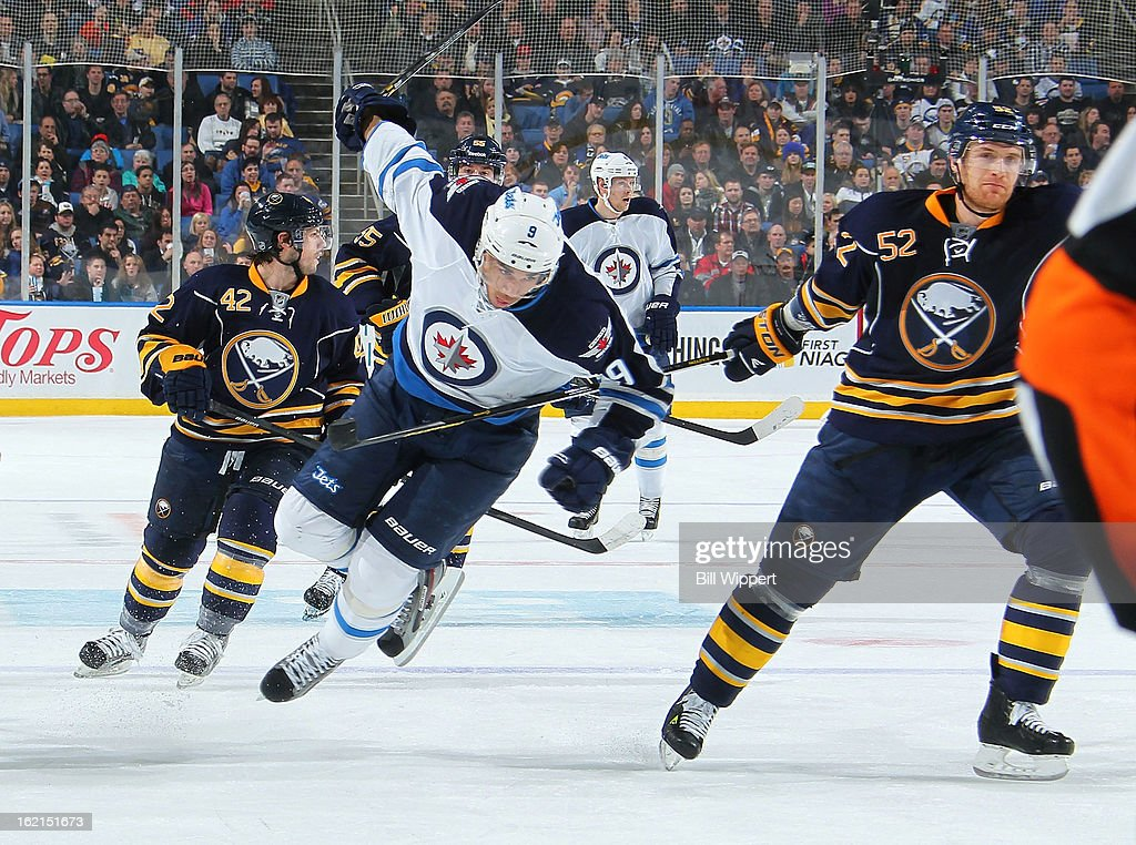 Evander Kane #9 of the Winnipeg Jets is upended by the stick of Alexander Sulzer #52 of the Buffalo Sabres on February 19, 2013 at the First Niagara Center in Buffalo, New York.