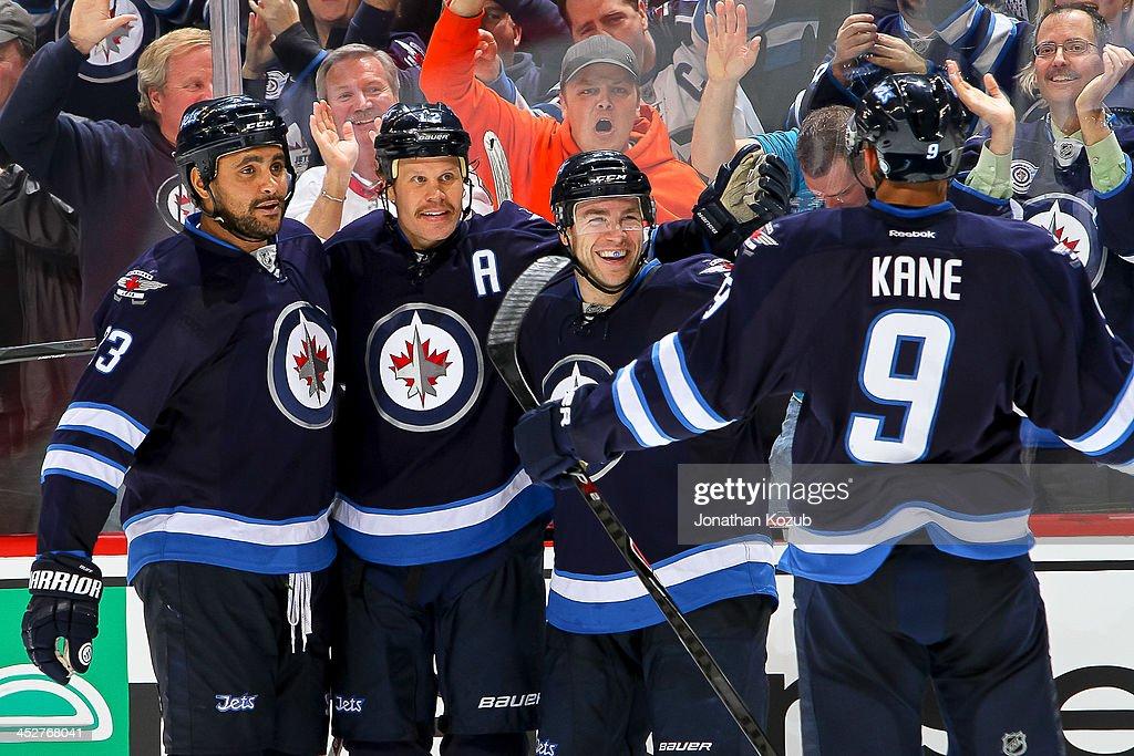 Evander Kane of the Winnipeg Jets joins teammates Dustin Byfuglien Olli Jokinen and Grant Clitsome of the Winnipeg Jets to celebrate a third period...