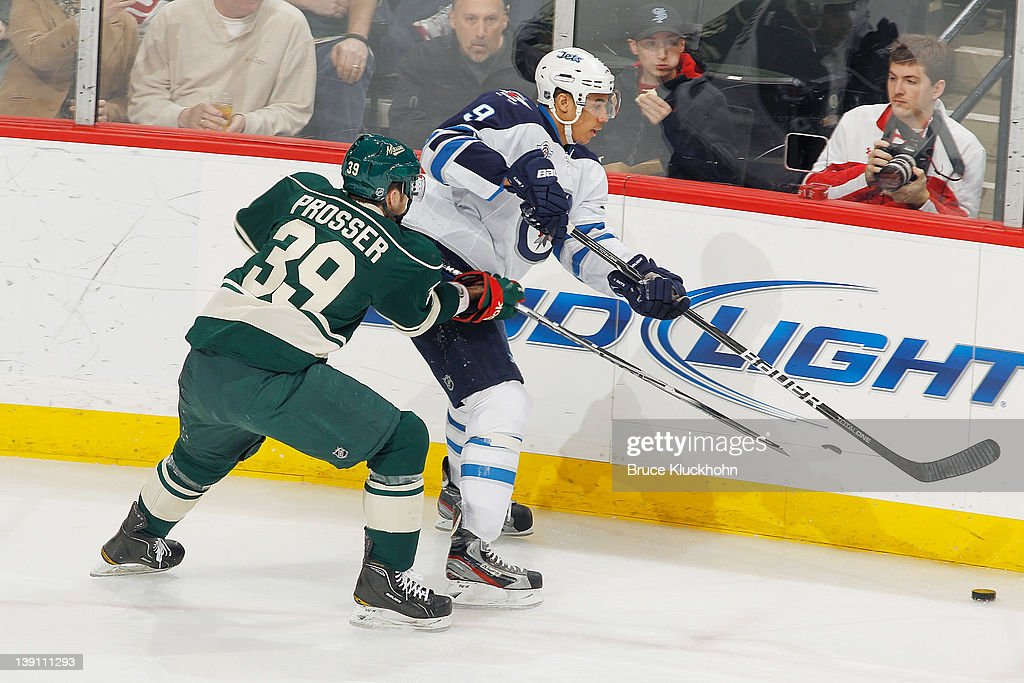 <a gi-track='captionPersonalityLinkClicked' href=/galleries/search?phrase=Evander+Kane&family=editorial&specificpeople=4303789 ng-click='$event.stopPropagation()'>Evander Kane</a> #9 of the Winnipeg Jets passes the puck while Nate Prosser #39 of the Minnesota Wild defends during the game at the Xcel Energy Center on February 16, 2012 in St. Paul, Minnesota.