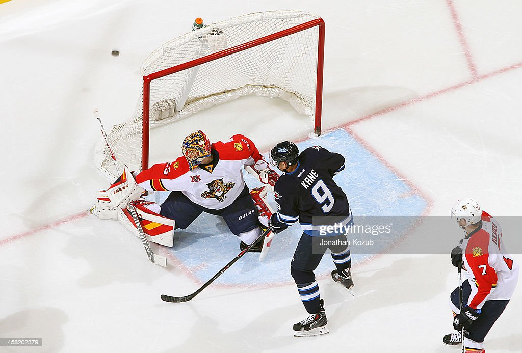 <a gi-track='captionPersonalityLinkClicked' href=/galleries/search?phrase=Evander+Kane&family=editorial&specificpeople=4303789 ng-click='$event.stopPropagation()'>Evander Kane</a> #9 of the Winnipeg Jets positions himself in front of goaltender <a gi-track='captionPersonalityLinkClicked' href=/galleries/search?phrase=Jacob+Markstrom&family=editorial&specificpeople=5370948 ng-click='$event.stopPropagation()'>Jacob Markstrom</a> #25 of the Florida Panthers as the puck flies wide of the net during second period action at the MTS Centre on December 20, 2013 in Winnipeg, Manitoba, Canada.