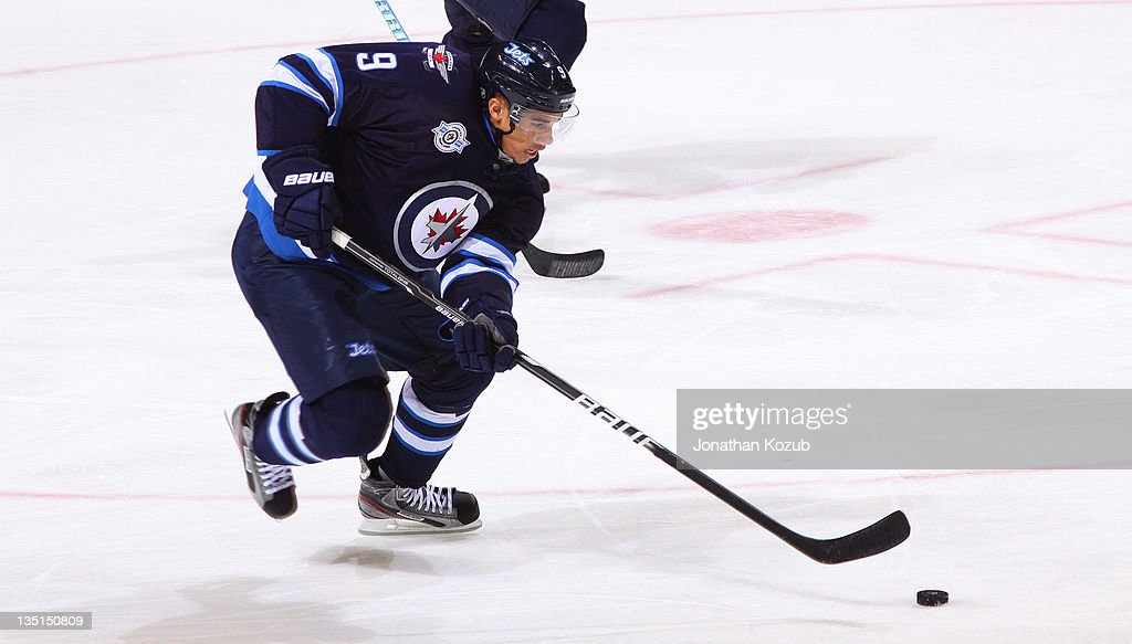 <a gi-track='captionPersonalityLinkClicked' href=/galleries/search?phrase=Evander+Kane&family=editorial&specificpeople=4303789 ng-click='$event.stopPropagation()'>Evander Kane</a> #9 of the Winnipeg Jets skates down the ice with the puck during third period action against the Boston Bruins at the MTS Centre on December 6, 2011 in Winnipeg, Manitoba, Canada.