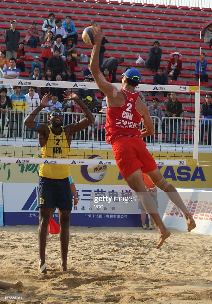 Evandro Goncalves Oliveira Junior (L) of Brazil defends against Peng Gao of China during the men's main draw of FIVB Beach Volleyball Shanghai Grand Slam at Jinshan City Beach on May 1, 2013 in Shanghai, China.