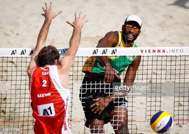 Evandro of Brazil spikes the ball against Ben Saxton of Canada during the Men's Quarterfinal match between Canada and Brazil on August 05 2017 in...