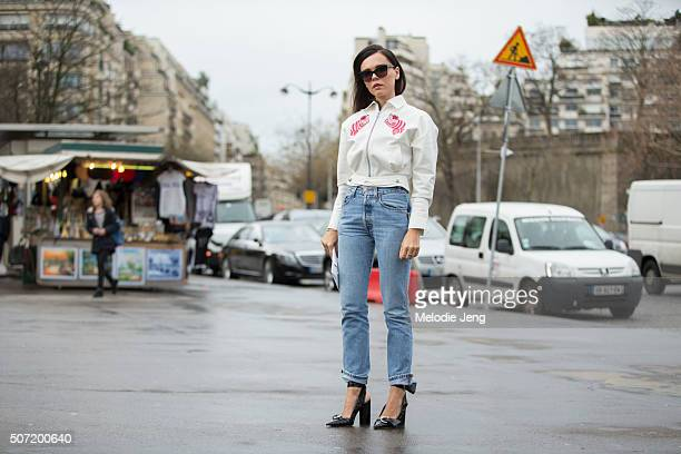 Evangelie Smyrniotaki wears an Olympia Le Tan ropped white zipped jacket with prints and 'Down the Rabbit Hole' princess print and Vetements jeans at...