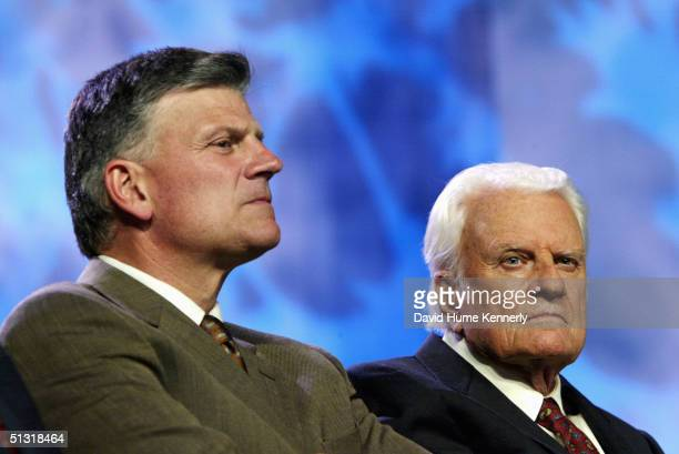 Evangelist Billy Graham and his son Franklin Graham look on at a Billy Graham rally on June 13 2003 in Oklahoma City Oklahoma