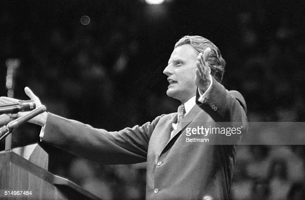 Evangelist Billy Graham arms thrown wide addresses revival meeting held in Madison Square Garden May 15th This is the first of a series of meetings...