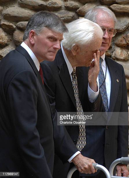 Evangelist Billy Graham center wipes his eye as he leaves the service with his son Franklin Graham left following the funeral for Ruth Graham at...