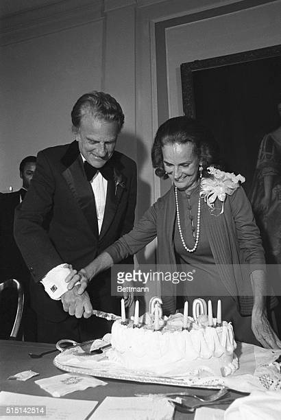 Evangelist Billy Graham gets a helping hand from his wife Ruth as he cuts his 60th birthday cake at a party given him 11/4 by local businessmen from...
