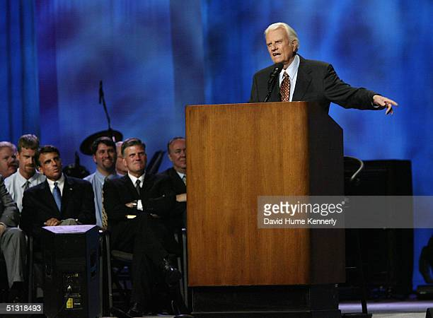 Evangelist Billy Graham speaks from the podium as son Franklin Graham listens at a Billy Graham rally on June 13 2003 in Oklahoma City Oklahoma...