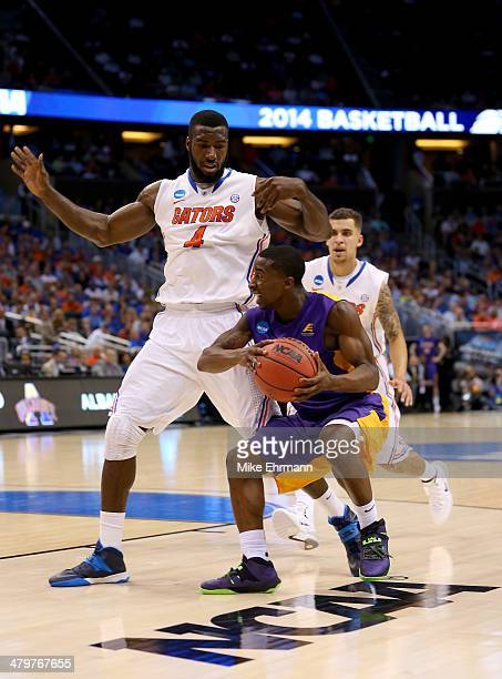 Evans of the Albany Great Danes with the ball against Patric Young of the Florida Gators in the first half during the second round of the 2014 NCAA...