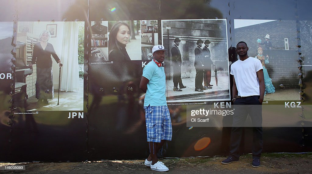 Evans Omondi (L) and Dan Walter Odamo, from Kenya, pose in front of a portrait of themselves in the photography exhibition 'The World in London' in Victoria Park on July 25, 2012 in London, England. The project, initiated by The Photographers' Gallery, aimed to commission portraits of 204 Londoners, each originating from one of the nations competing in the London 2012 Olympic Games. The project has taken three years to come to fruition and the Photographers' Gallery is still seeking to find sitters from six nations to complete the full set, namely: American Samoa, FS Micronesia, Guam, Marshall Islands, Nauru and Palau.