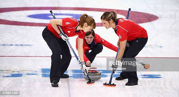 Eve Muirhead of Great Britain plays a stone as Claire Hamilton and Vicki Adams assist during the Bronze medal match between Switzerland and Great...