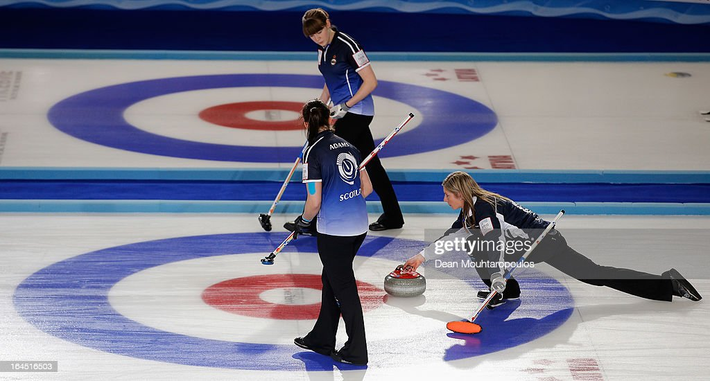 Eve Muirhead (R) of Scotland throws the stone as team mates as Vicki Adams and Claire Hamilton sweep during the Gold medal match between Sweden and Scotland on Day 9 of the Titlis Glacier Mountain World Women's Curling Championship at the Volvo Sports Centre on March 24, 2013 in Riga, Latvia.