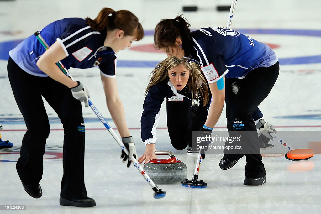 Eve Muirhead (C) of Scotland throws the stone as team mates as Vicki Adams and Claire Hamilton sweep during the Gold medal match between Sweden and Scotland on Day 9 of the Titlis Glacier Mountain World Women's Curling Championship at the Volvo Sports Centre on March 24, 2013 in Riga, Latvia.
