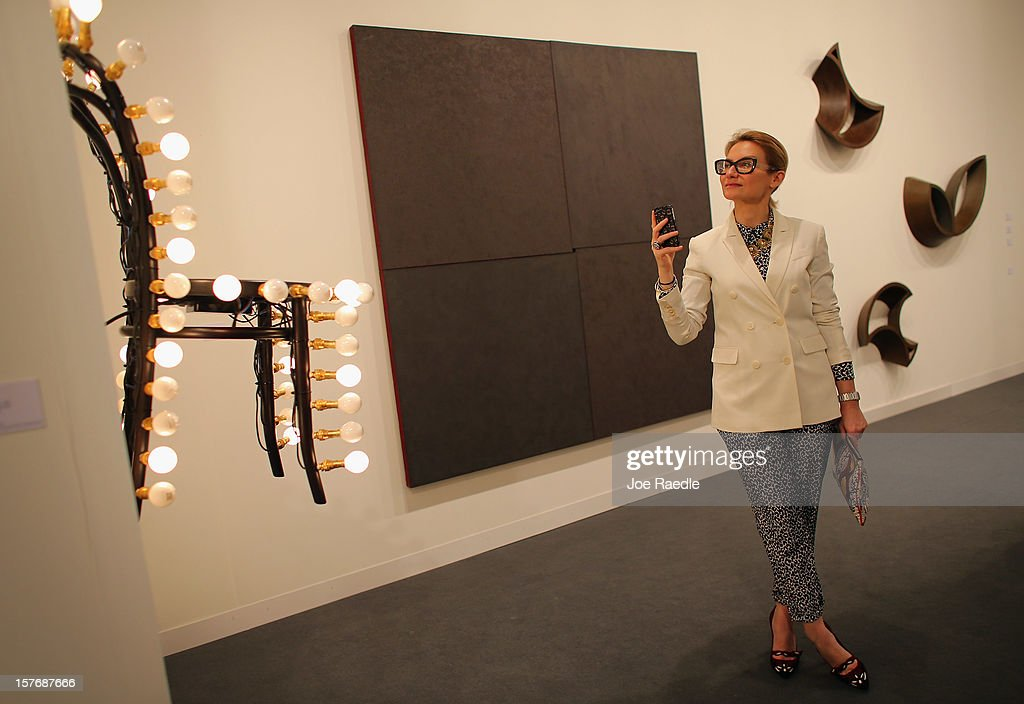 Evelina Khromtchenko looks at the art in a gallery as Art Basel opens at the Miami Beach Convention Center on December 5, 2012 in Miami Beach, Florida. The 11th edition of the art show runs from December 6 through the 9th.