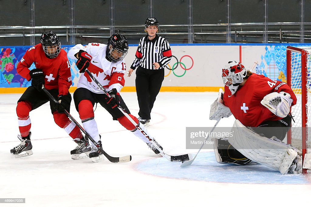 Evelina Raselli #14 of Switzerland and Caroline Oullette #13 of Canada fight for the puck in front of the net of <a gi-track='captionPersonalityLinkClicked' href=/galleries/search?phrase=Florence+Schelling&family=editorial&specificpeople=723566 ng-click='$event.stopPropagation()'>Florence Schelling</a> #41 of Switzerland during the Women's Ice Hockey Playoffs Semifinal game on day ten of the Sochi 2014 Winter Olympics at Shayba Arena on February 17, 2014 in Sochi, Russia.