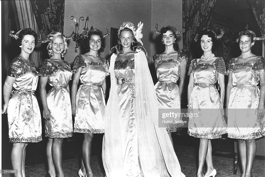 Evelyn Ay the newly crowned Miss America from Ephrata Pennsylvania stands in her cape and gown surrounded by a court of six young women c 1954