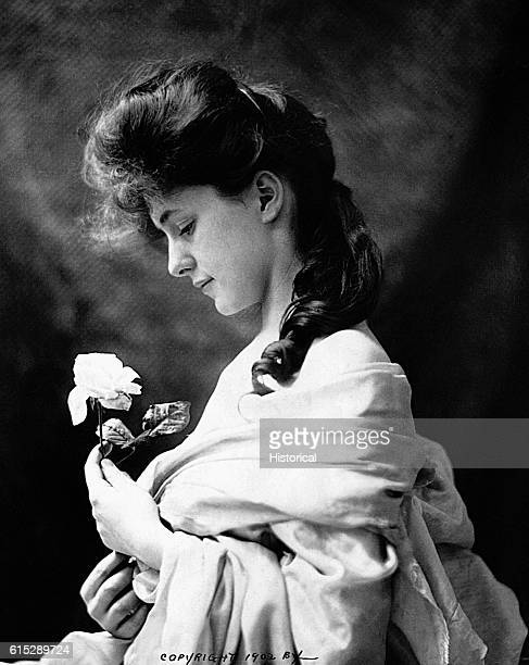 Evelyn Nesbit the celebrated ideal Gibson Girl of New York society in a romantic profile portrait holding a rose She was involved as a young girl...