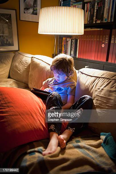 evening, boy on couch with tablet computer