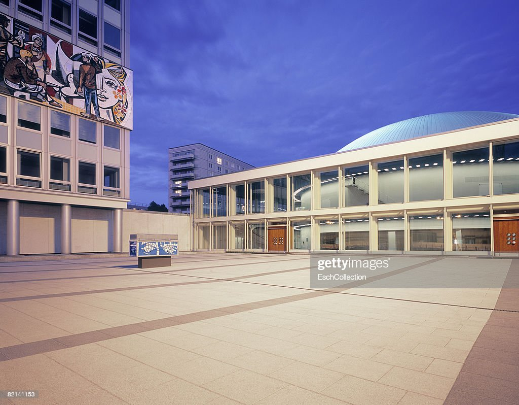 Evening image of square in Berlin with on the left; a building from the former DDR (Haus der Gesundheid) with a large mosaic tile picture.