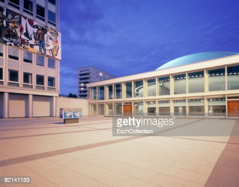 Evening image of square in Berlin with on the left; a building from the former DDR (Haus der Gesundheid) with a large mosaic tile picture. : Foto de stock