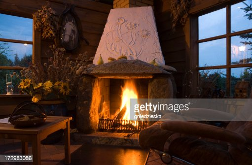 Cozy Living Room With Fireplace evening in a cozy living room with a large fireplace stock photo