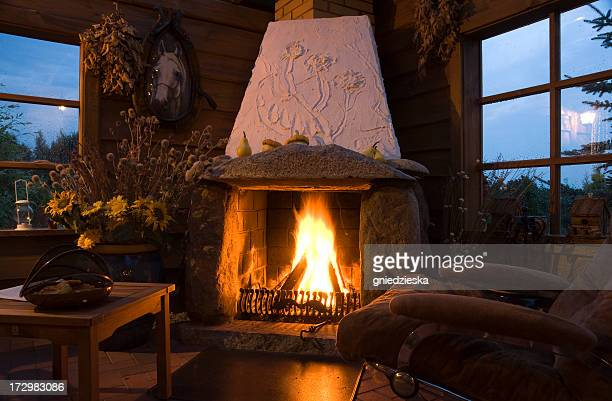 Evening in a cozy living room with a large fireplace