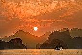 Evening sunset in  Ha long Bay Vietnam with a junk cruising