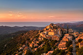 The Balagne village of Speloncato in Corsica bathed in late evening sunshine with the Regino valley and Mediterranean sea behind and pink, orange and deep blue skies above